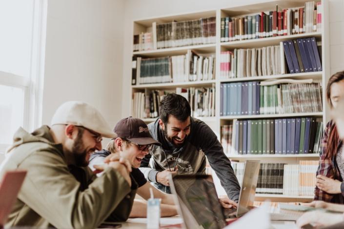 joukko nuoria miehiä katsomassa tietokoneen näyttöä