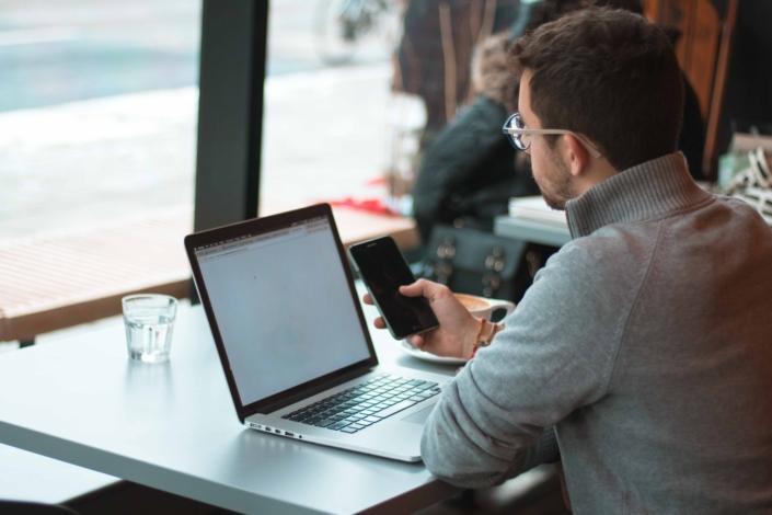 Mies käyttää tietokonetta ja matkapuhelinta kahvilassa